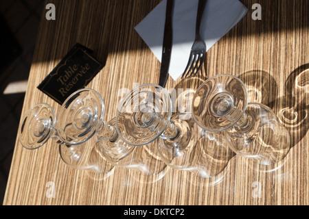 Verres à vin à l'envers sur une table à l'extérieur d'un restaurant Casting Shadows Banque D'Images