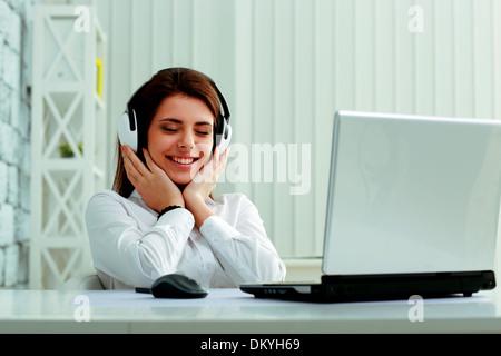 Belle jeune businesswoman listening music in headphones at office Banque D'Images