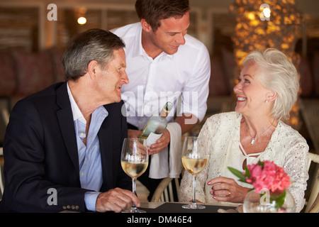 Waiter Serving Wine pour Senior Couple In Restaurant Banque D'Images