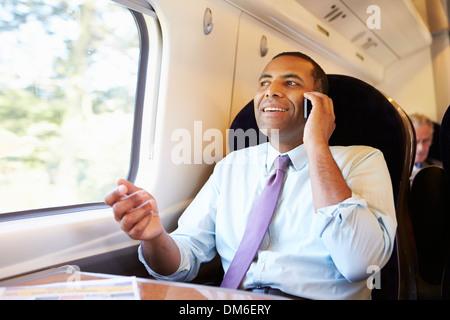D'affaires pour se rendre à son travail sur le train à l'aide de Mobile Phone Banque D'Images