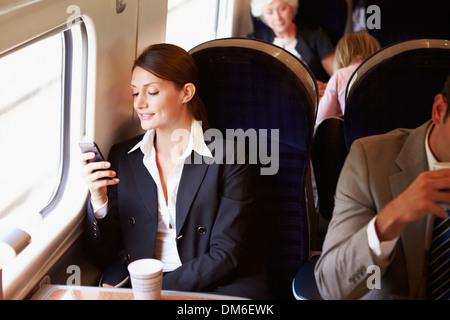 Businesswoman pour se rendre à son travail sur le train à l'aide de Mobile Phone Banque D'Images