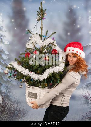 La femme est d'avoir ramené l'arbre de Noël décoré Banque D'Images