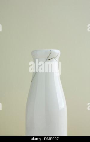 La rupture d'un pot de lait ou vase a été fixé, montrant des fissures, sur un fond crème. Banque D'Images
