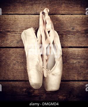 Chaussures de ballet rose vieille pendaison sur fond de bois Banque D'Images