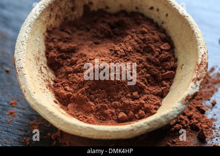 La poudre de cacao dans un bol sur fond noir, close-up
