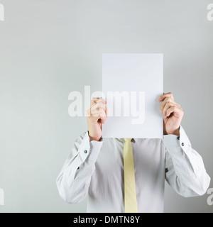 Man holding blank white board sur son visage sur fond blanc Banque D'Images
