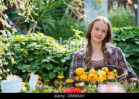 L'été sur une ferme biologique. Une jeune fille tenant un panier de légumes courges fraîches. Banque D'Images