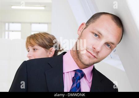 Un jeune homme en costume et chemise rose appuyé contre un mur et une jeune femme en arrière-plan.