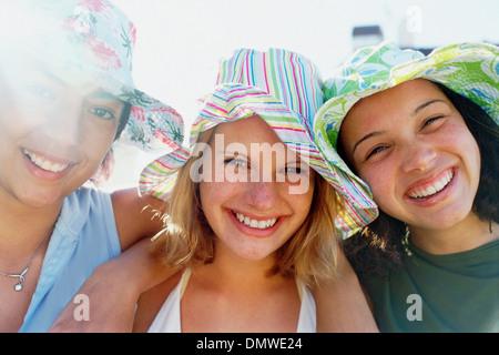 Trois jeunes filles dans une ligne portant des sunhats looking at camera et souriant.