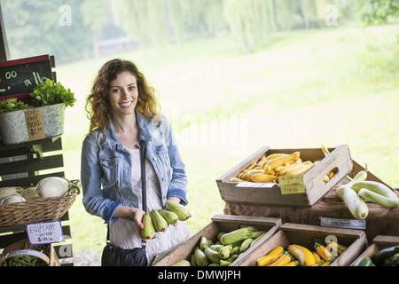 Une ferme de fruits et légumes biologiques. Une jeune femme le tri des légumes. Banque D'Images