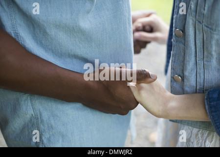 Un jeune homme et femme un couple holding hands. Banque D'Images