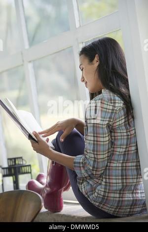 Une jeune femme en train de lire un livre. Banque D'Images