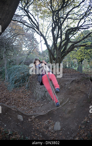 Une jeune fille de 11 ans, balançoires sur une corde Banque D'Images