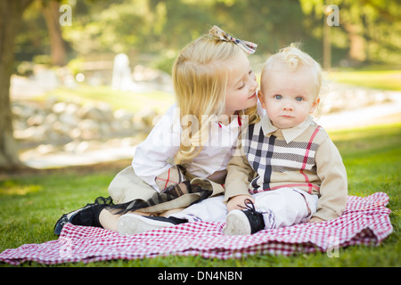 Petite fille douce embrasse petit frère sur sa joue à l'extérieur dans le parc. Banque D'Images
