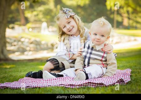 Petite fille douce épouse son petit frère sur une couverture de pique-nique en plein air au parc. Banque D'Images