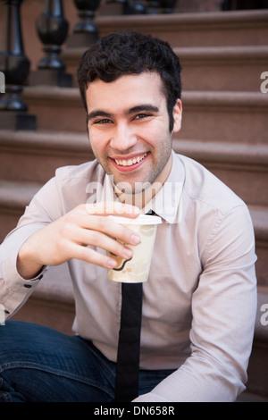 Hispanic businessman de boire du café sur les marches Banque D'Images