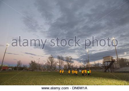 L'équipe féminine de soccer sur terrain au crépuscule Banque D'Images
