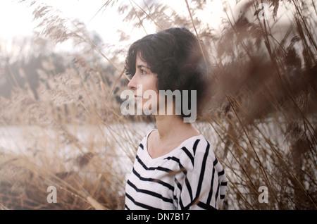 Portrait d'une femme entre les hautes herbes en hiver Banque D'Images