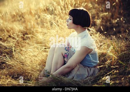 Jeune femme assise sur un pré, portrait Banque D'Images
