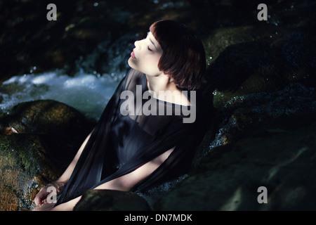 Jeune femme est assise sur un creek Banque D'Images