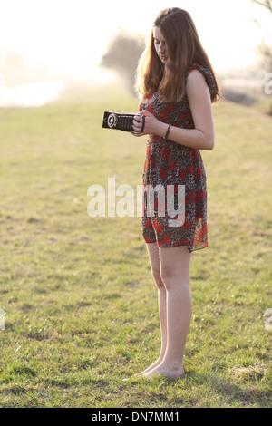 Jeune femme sur une prairie avec caméra nostalgique Banque D'Images