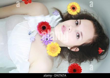 Jeune femme avec des fleurs dans la baignoire Banque D'Images