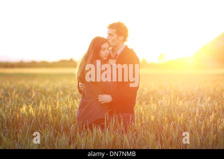 Jeune couple dans l'amour dans le champ de maïs, des baisers en rétro-éclairage Banque D'Images