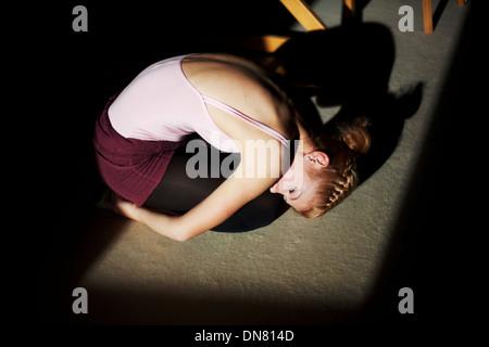 Jeune femme à genoux sur le sol, portrait Banque D'Images