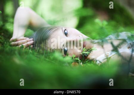 Fille couchée sur le sol de la forêt, portrait Banque D'Images