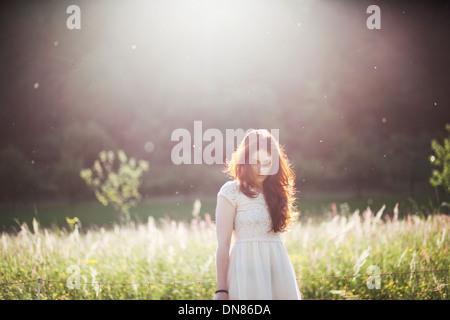 Jeune femme debout sur une prairie en contre-jour, portrait Banque D'Images