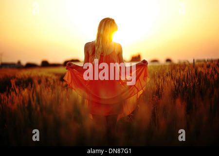 Robe femme debout dans le champ de blé au coucher du soleil Banque D'Images