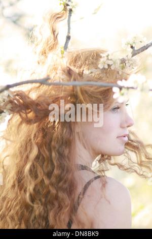 Femme aux longs cheveux entre branches fleuries, portrait Banque D'Images