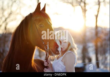 Jeune femme en robe blanche à cheval en hiver