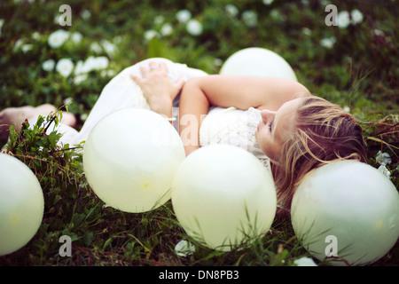 Jeune femme couchée sur un pré entre balloons Banque D'Images
