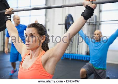 Femme déterminée faisant traverser monter en salle de sport Banque D'Images