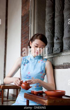 Jeune femme portant et cheongsam holding teapot Banque D'Images