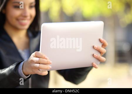 Close up of a woman holding et regardant une tablette numérique dans un parc Banque D'Images