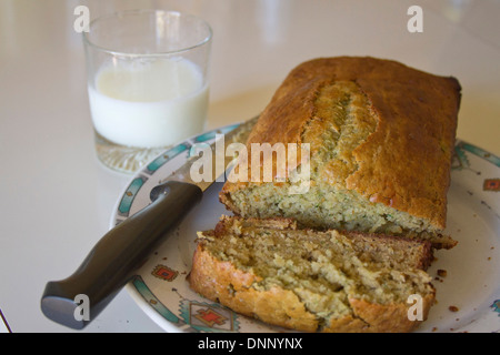 Close up pf un accueil chaleureux, des tranches de miche de pain de courgettes sur une assiette à côté d'un verre Banque D'Images