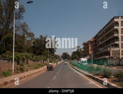 Man pushing trolley et la circulation sur route forestière Nairobi Kenya Banque D'Images