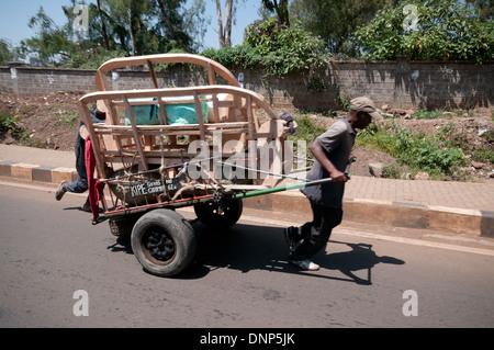 Les hommes luttent avec chariot lourdement chargé transportant meubles sur Forest Road Nairobi Kenya Nairobi KENYA Banque D'Images
