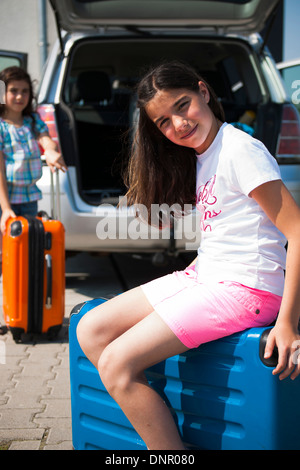 Girl Sitting on Suitcase et chargement Van pour vacances, Mannheim, Baden-Wurttemberg, Germany Banque D'Images