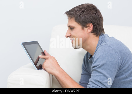 Smiling young man using digital tablet in living room Banque D'Images