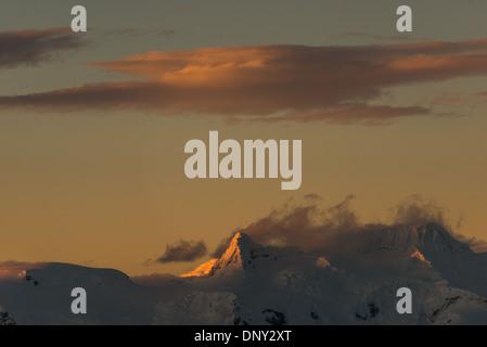 L'ANTARCTIQUE - le soleil couchant jette une lueur orange magnifique sur les nuages et les montagnes de l'Antarctique Banque D'Images