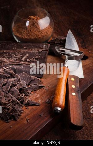 Couper les barres de chocolat et le cacao en poudre sur une table en bois Banque D'Images