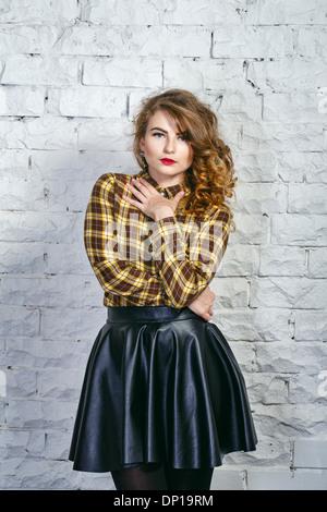Charmante fille en jupe en cuir et chemise à carreaux
