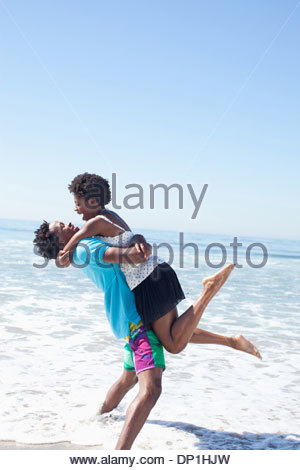 Man carrying woman on beach Banque D'Images