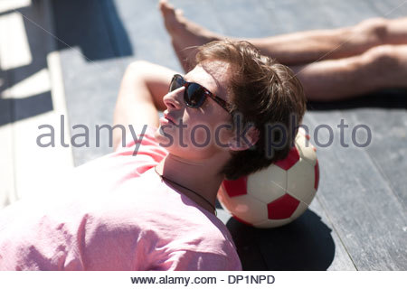 Man resting head on soccer ball Banque D'Images