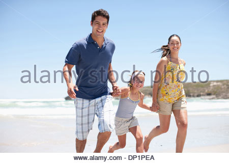 Family running on beach Banque D'Images