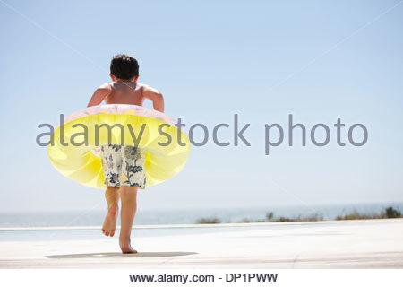 Garçon avec anneau gonflable faisant un pas hors de la piscine à débordement Banque D'Images