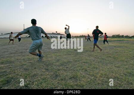Juin 04, 2006; BAGDAD, IRAK, soldats irakiens hors-service jouer un match de football au crépuscule dans un champ Banque D'Images